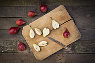 Whole and sliced organic red Clapp's Favourites, wooden board and kitchen knife on dark wood - LVF003901