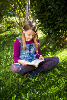 Little girl sitting on a meadow in the garden reading a book - SARF002111