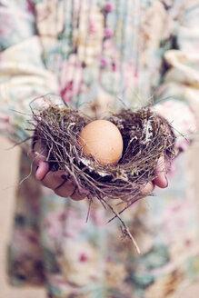 Girl holding an egg in a nest - XCF000027