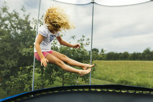 Girl bouncing on trampoline - MGOF000795