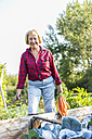 Smiling senior woman at vegetable patch - UUF005728
