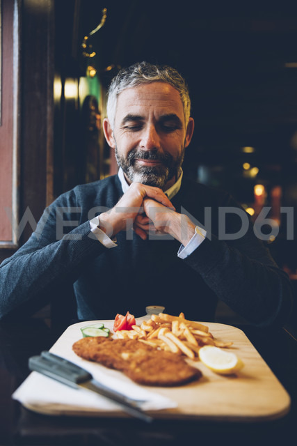 Smiling man in restaurant having Wiener Schnitzel with French fries - AIF000091