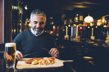 Smiling man in restaurant having Wiener Schnitzel with French fries - AIF000094
