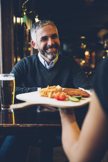 Smiling man in restaurant receiving Wiener Schnitzel with French fries - AIF000097