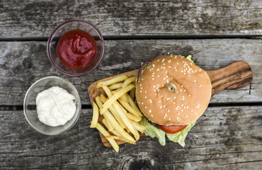 Homemade burger with lettuce, meat, tomato, onion and french fries on chopping board - SARF002138