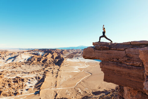 Chile, Atacama Desert, woman standing in yoga pose on a cliff - GEMF000396