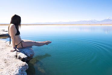 Chile, Atacama Desert, woman in bikini dipping her feet in Laguna Cejar - GEMF000402