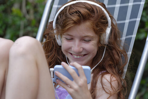 Happy girl hearing music with headphones looking at smartphone - LBF001214