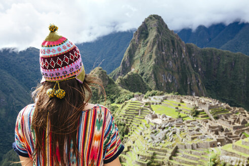 Peru, Machu Picchu region, Female traveler looking at Machu Picchu citadel and Huayna mountain - GEMF000410