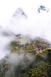 Peru, Machu Picchu region, Machu Picchu citadel and Huayna mountain in fog - GEMF000416