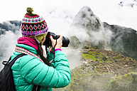 Peru, Machu Picchu region, Travelling woman taking picture of Machu Picchu Citadel - GEMF000419