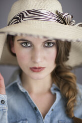 Portrait of rouged young woman with brown hair wearing summer hat - NNF000235