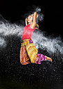 Young woman jumping in between cloud of flour in front of night sky - STSF000942