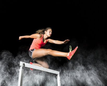Young woman jumping over hurdle - STSF000945