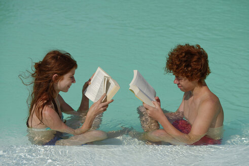 Redheaded girl and boy sitting at  pool edge reading a book - LBF001222