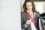 Young woman holding folder looking at cell phone - UUF005749