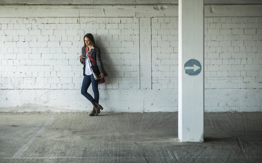 Young woman in a car park holding folder and looking at cell phone - UUF005752