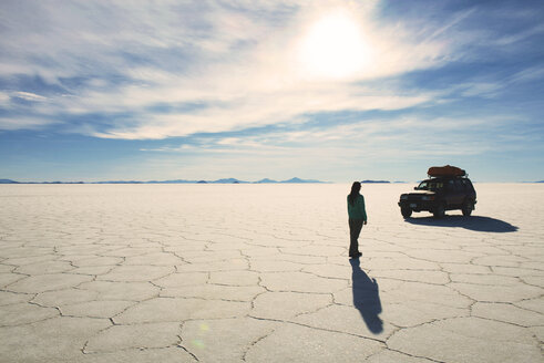 Bolivia, Potosi, Woman walking towards her 4x4 in Uyuni salt flats - GEMF000425