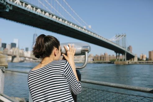 USA, New York City, young woman using coin operated binoculars - GIOF000131