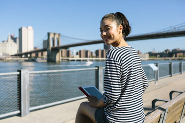 USA, New York City, portrait of smiling young woman with digital tablet sitting on backrest of a bench - GIOF000137
