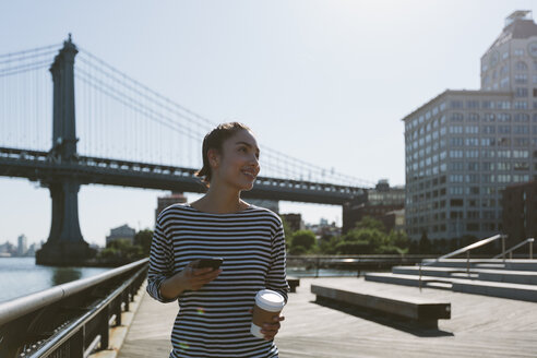 USA, New York City, portrait of young woman with smartphone and coffee to go - GIOF000140