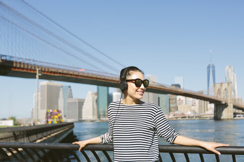 USA, New York City, portrait of young woman hearing music with headphones in front of the skyline - GIOF000146