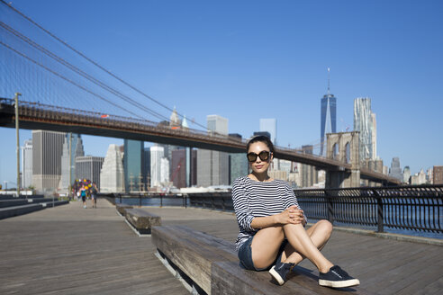 USA, New York City, portrait of young woman relaxing on a bench in front of Brooklyn Bridge - GIOF000149