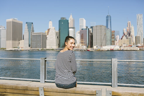 USA, New York City, young woman sitting in front of the skyline looking over her shoulder - GIOF000152