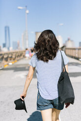 USA, New York City, back view of young woman walking on Brooklyn Bridge - GIOF000155