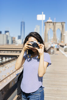 USA, New York City, young woman standing on Brooklyn Bridge taking a photo with camera - GIOF000158