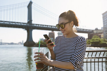 USA, New York City, portrait of smiling young woman with soft drink looking at smartphone - GIOF000161