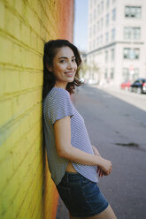 Portrait of smiling young woman leaning against yellow brick wall - GIOF000164