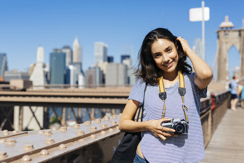 USA, New York City, portrait of smiling young woman with camera standing on Brooklyn Bridge - GIOF000167