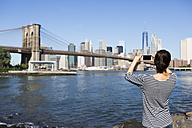 USA, New York City, back view of young woman taking a photo of Brooklyn Bridge with smartphone - GIOF000170