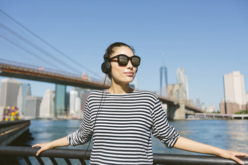 USA, New York City, portrait of  young woman with headphones and sunglasses in front of skyline - GIOF000173