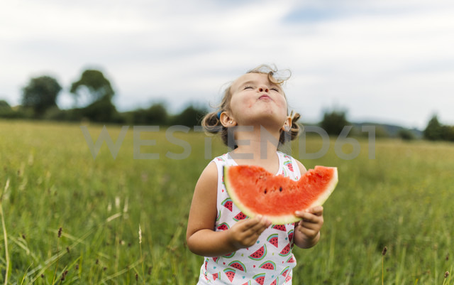 Little girl eating watermelon on a meadow - MGOF000802
