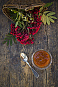 Wickerbasket, rowanberries and glass of rowanberry jam on dark wood - LVF003936