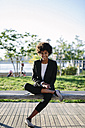 USA, New York City, portrait of smiling businesswoman sitting on a bench with digital tablet - GIOF000179