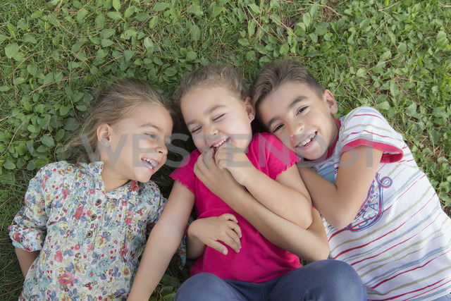 Portrait of three laughing children lying side by side on a meadow - ERLF000056 - Enrique Ramos/Westend61