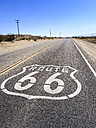 USA, California, Route 66 with sign on road, desert - SBDF002262