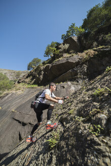 Spain, Galicia, A Capela, Ultra trail runner ascending a slope of rock - RAEF000525