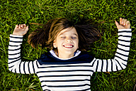 Portrait of girl wearing striped sweatshirt lying on a meadow with closed eyes - LVF003958