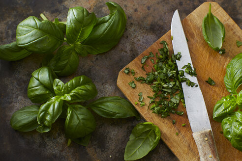 Whole and chopped basil leaves and kitchen knife on wooden board - KSWF001583