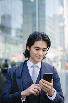 USA, New York City, businessman looking at cell phone in Manhattan - GIOF000214