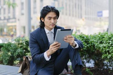 USA, New York City, Manhattan, businessman looking at digital tablet - GIOF000223