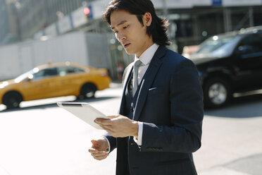 USA, New York City, businessman looking at digital tablet in Manhattan - GIOF000229