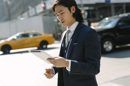 USA, New York City, businessman looking at digital tablet in Manhattan - GIOF000229