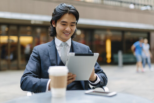 USA, New York City, smiling businessman at outdoor cafe looking at digital tablet - GIOF000235