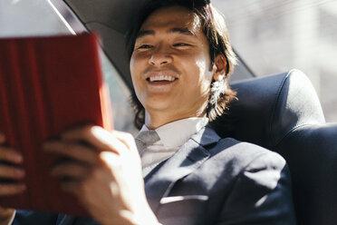 Smiling businessman on back seat of car using digital tablet - GIOF000241