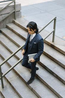 Businessman walking downstairs holding digital tablet - GIOF000244
